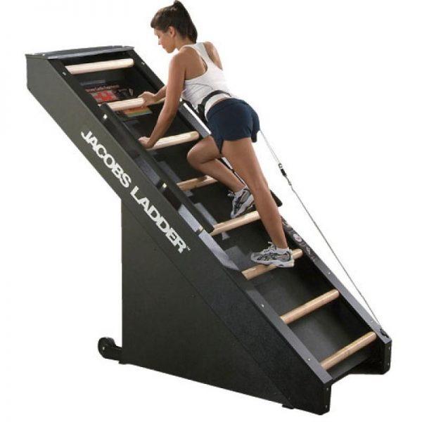 Black Jacob's Ladder stair climbing machine. wood maple rungs on Jacob's Ladder, woman climbing.