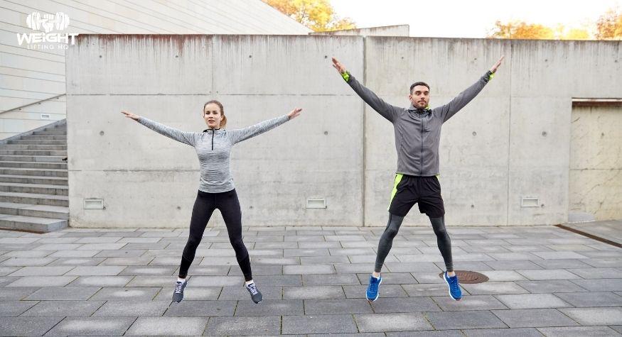 man and woman doing jumping jacks